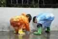 Young Children In The Rain With Raincoats