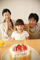 Mid adult couple sitting with their daughter in front of a birthday cake