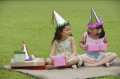 Two girls wearing party hats sitting on picnic blanket  holding pink gift boxes