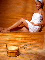 Women wrapped in towel  sitting in sauna  smiling