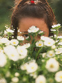 Young girl hiding behind flowers