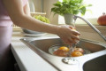 Woman Washing Assorted Fruit In Sink