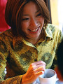 Young woman stirring a cup of coffee  smiling