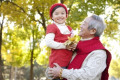 Grandfather Holding Granddaughter Holding Maple Leaves