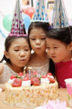 Three girls celebrating a birthday  blowing birthday candles