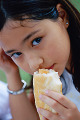 Young girl eating sausage bun  close-up