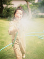 Young girl spraying water with hose