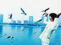 Young woman with city in background  seagulls flying