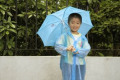 Young Child In The Rain With An Umbrella