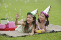 Two girls wearing party hats lying on picnic blanket  looking at bubbles