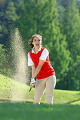 Sand explosion as a female golfer plays a bunker shot