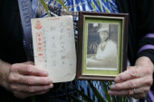 72nd Anniversary of Japan s Surrender in WWII at Yasukuni Shrine A woman holds a picture and a postcard from her relative who fought during the