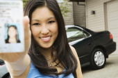 Asian teenager proudly showing new driver´s license