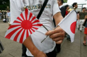 72nd Anniversary of Japan s Surrender in WWII at Yasukuni Shrine A man holds war flags of the Imperial Japanese Army to pay his respects to the