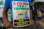 72nd Anniversary of Japan s Surrender in WWII at Yasukuni Shrine A man holds a placard with the message  Tokyo 2020 Yes  Taiwan N